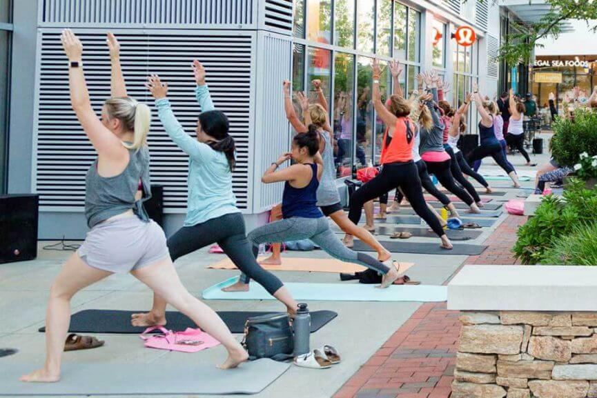 Women doing yoga poses outside on the sidewalk