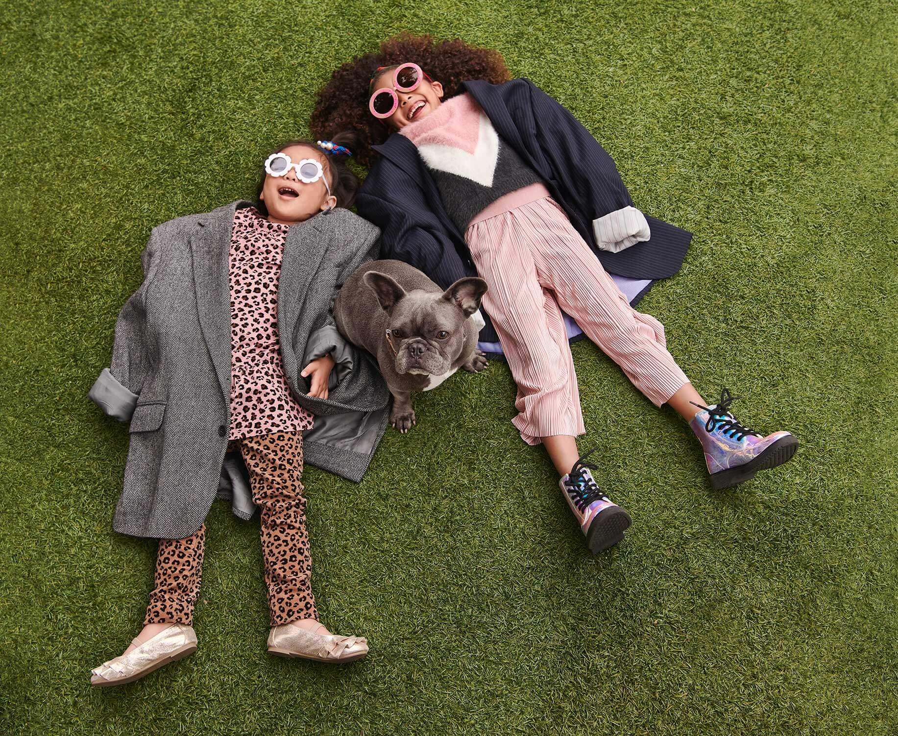 Kids with sunglasses laying on the lawn with a french bulldog.