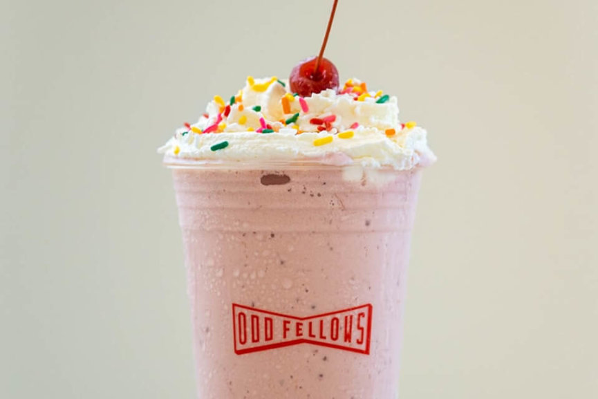 Strawberry milkshake with whipped cream and rainbow sprinkles