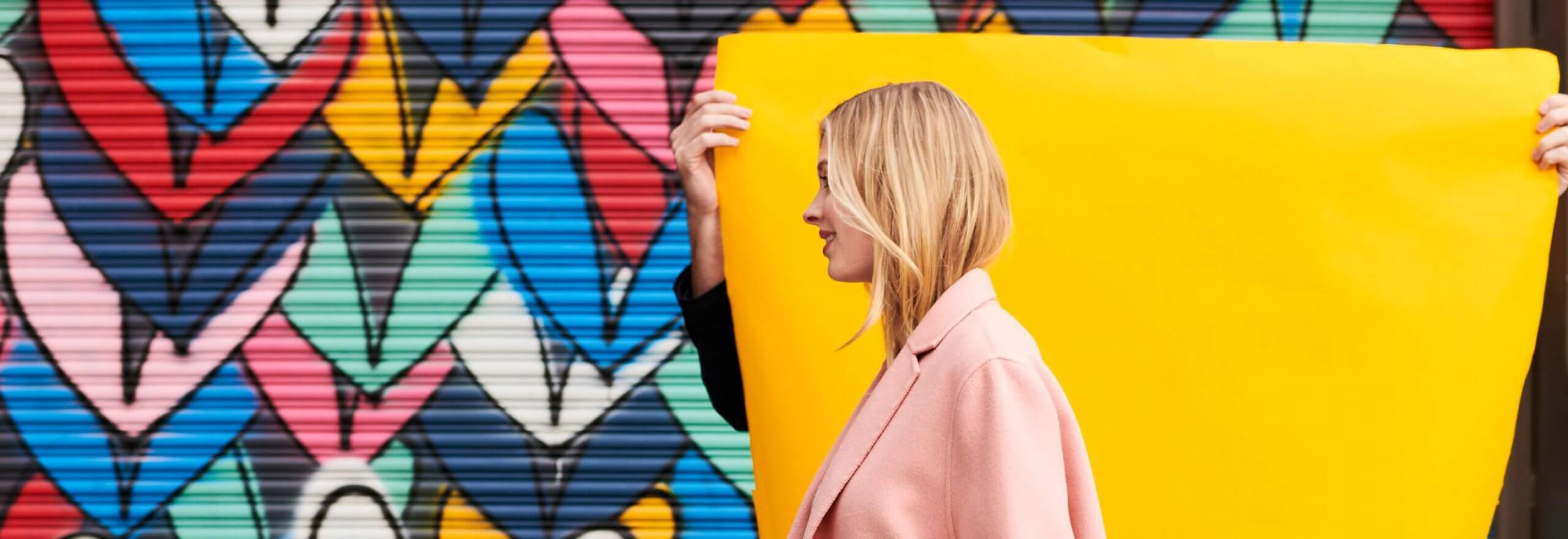 Woman walking in front of art mural